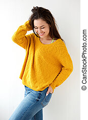 beautiful young woman smiling in yellow sweater against white wall