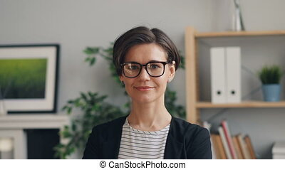 Portrait of beautiful young woman smiling looking at camera standing in office