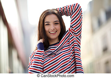 beautiful young woman smiling outside with hand in hair