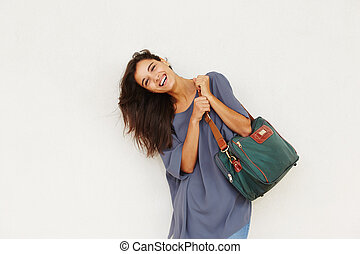 beautiful young woman smiling with bag against white wall