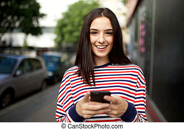 beautiful young woman smiling with cellphone outside