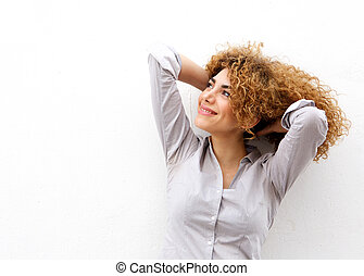 beautiful young woman smiling with hand in hair looking up