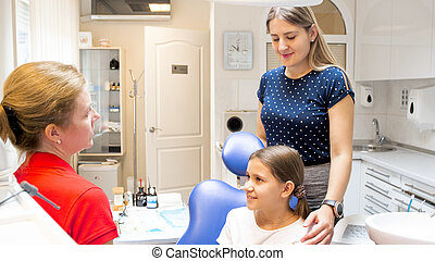 Portrait of beautiful young woman standing behind her daughter sitting in dentist chair at clinic