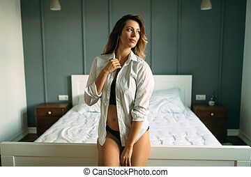 Portrait of beautiful young woman standing in bedroom