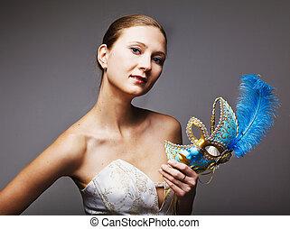 Portrait of beautiful young woman wearing blue carnival mask