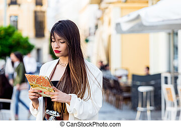 portrait of Beautiful young woman tourist looking at the map