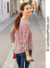 beautiful young woman walking along a street with luggage and looking over her shoulder