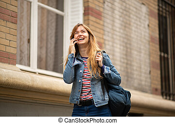 beautiful young woman walking and talking with mobile phone in city