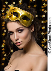 Portrait of beautiful young woman wearing golden party mask