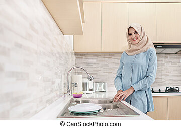 beautiful young woman wearing hijab washing the dishes