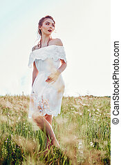 Portrait of beautiful young woman wearing white dress in field