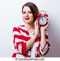 portrait of beautiful young woman with alarm clock on the wonderful white studio background