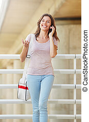beautiful young woman with bag talking on cell phone