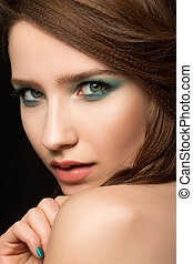 Portrait of beautiful young woman with blue nails and eye makeup looking over her shoulder