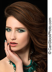 Portrait of beautiful young woman with blue nails and eye makeup touching her face