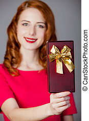 portrait of beautiful young woman with cute gift on the wonderful grey studio background