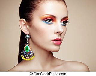 Portrait of beautiful young woman with earring. Jewelry and accessories. Perfect makeup. Fashion photo