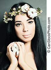 Portrait of Beautiful Young Woman with Flowers. Perfect Makeup and Skin.