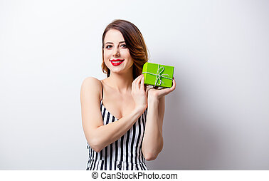 portrait of beautiful young woman with gift on the wonderful white studio background