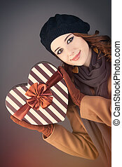 portrait of beautiful young woman with heart shaped gift on the wonderful grey studio background