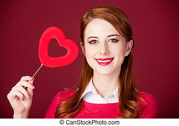 portrait of beautiful young woman with heart shaped toy on the wonderful red studio background