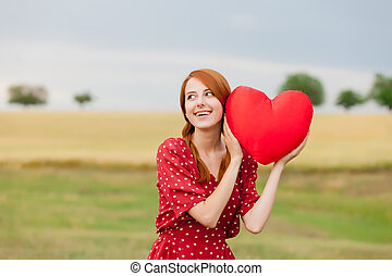 portrait of beautiful young woman with heart shaped toy on the wonderful wheat field background