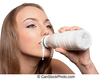 Portrait of beautiful young woman with milk on white background