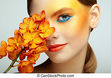 Portrait of beautiful young woman with orchid