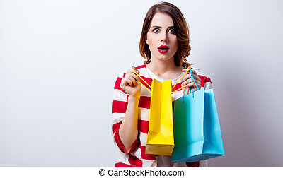 portrait of beautiful young woman with shopping bags on the wonderful white studio background