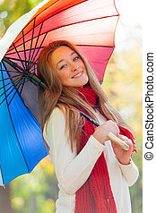 portrait of beautiful young woman with umbrella on the wonderful autumn park background