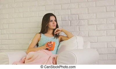 Portrait of beautiful young woman with cup of coffee or tea