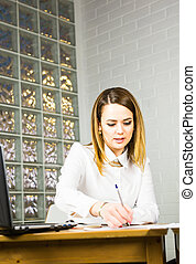 Portrait of beautiful young woman working in her office.