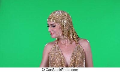 Portrait of beautiful young women is looking straight and dancing. A bright makeup gold dress and headdress on a green screen in the studio