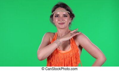 Portrait of beautiful young women is looking straight and dancing. A burning brunette in an orange fringed dress on a green screen in the studio