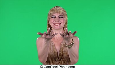 Portrait of beautiful young women is looking straight coquettishly waving hand and showing gesture you come here. A bright makeup gold dress and headdress on a green screen in the studio