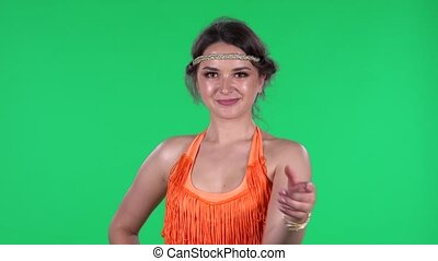 Portrait of beautiful young women is looking straight coquettishly waving hand and showing gesture come here. A burning brunette in an orange fringed dress on a green screen in the studio