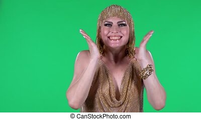 Portrait of beautiful young women is looking straight with shocked and surprised wow face expression. A bright makeup gold dress and headdress on a green screen in the studio