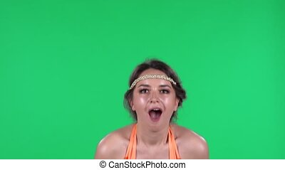 Portrait of beautiful young women is looking straight with shocked and surprised wow face expression. A burning brunette in an orange fringed dress on a green screen in the studio