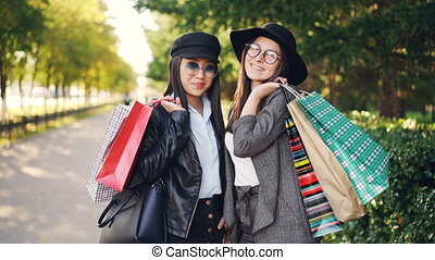 Portrait of beautiful young women shoppers standing in the street holding paper bags and smiling looking at camera. Youth lifestyle and consumerism concept.