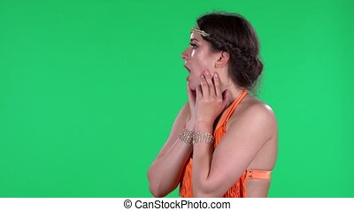 Portrait of beautiful young women with shocked and surprised wow face expression. A burning brunette in an orange fringed dress on a green screen in the studio. Side view