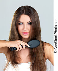 Portrait of beauty - Beautiful woman is brushing her long...