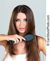 Portrait of beauty - Beautiful woman is brushing her long...