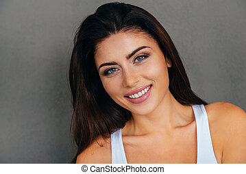 Portrait of beauty. Beautiful young woman in white tank top looking at camera and smiling while standing against grey background