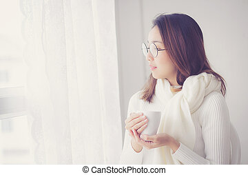 Portrait of bedroom concept: asian woman holding a cup of coffee with on bedroom in breakfast time.