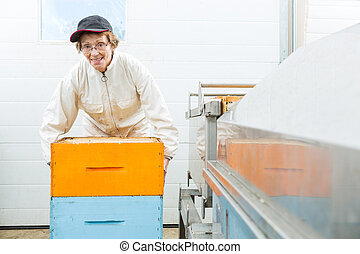 Portrait Of Beekeeper With Honeycomb Crates At Factory
