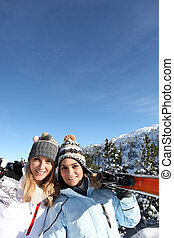 portrait of best friends at ski resort against deep blue sky background