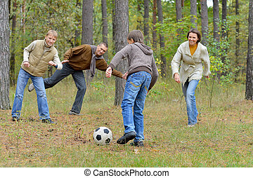 Portrait of big happy family playing football in park