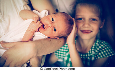 portrait of big sister with newborn baby