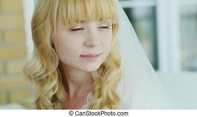 Portrait of blond bride who looks in the mirror