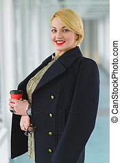 Portrait of blond businesswoman holding coffee and glass in...